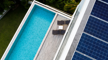 Photo pour Top view of outdoor swimming pool and solar panels on the roof of villa - image libre de droit