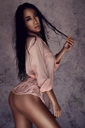 Foto de Sensusal beauty in wet pink shirt and white panties. Sexy beautiful woman posing over concrete wall background - Imagen libre de derechos