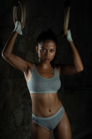 Sexy brunette fitness woman at the gym. Female athlete looking into the camera while standing at gym holding dip rings