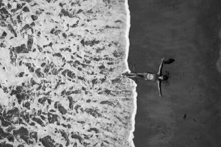 Photo pour Black and white photo - aerial top view of woman with her hands outstretched laying on the sandy beach near the ocean. Summer holiday concept - image libre de droit