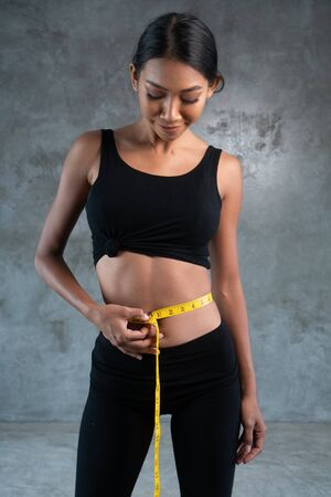 Photo for Portrait of fitness beautiful and smiling female model with measuring tape posing at the fitness gym - Royalty Free Image