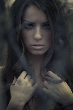 Beautiful young topless woman posing outdoors. Dark mysterious artistic portrait.