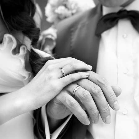 Hand of the groom and the bride with wedding rings. Monochrome image.