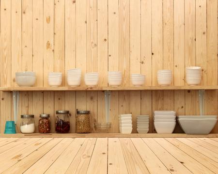 White ceramic kitchenware on the wooden shelf