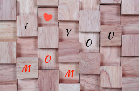wood background : message I love you mom spelled in wooden block
