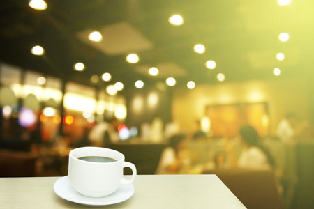Blurred background : white cup of coffee and customer at restaurant blur background with bokeh