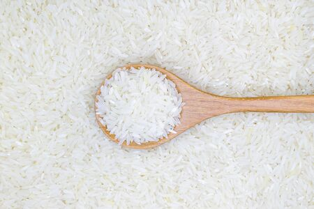jasmine rice in wooden spoon over jasmine rice background, Selective focusの写真素材