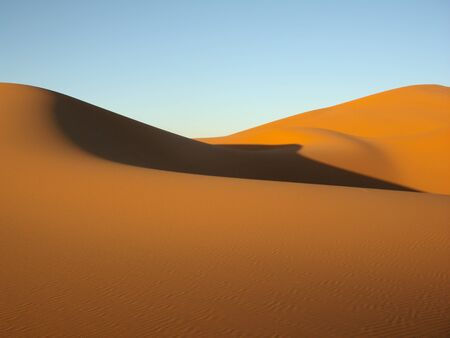 Sand dunes in the desert with blue sky