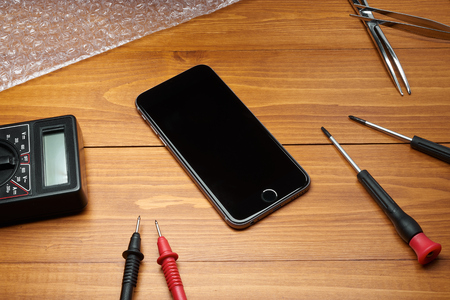 Repaired smartphone with tools on table in wood