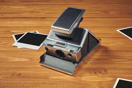 Photo pour Polaroid camera and film on wood table - image libre de droit