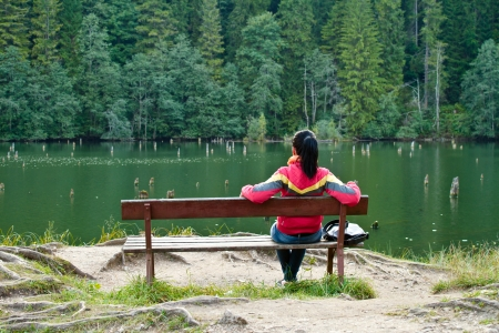 Woman sitting on a bench near the lake
