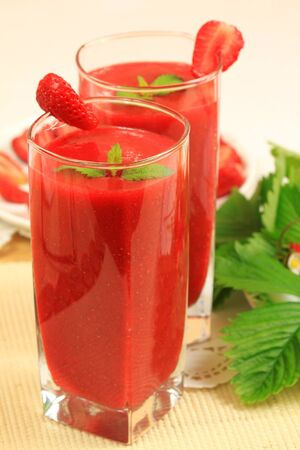 Strawberry smoothies with fresh fruits and lemon balm leaves