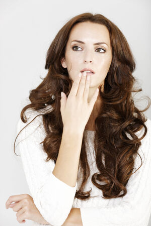 Young woman with her hand on her chin expressing concern