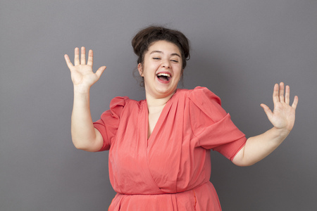 success concept - extrovert young fat girl dancing wearing a vintage dress with both hands raised expressing her achievement and happiness