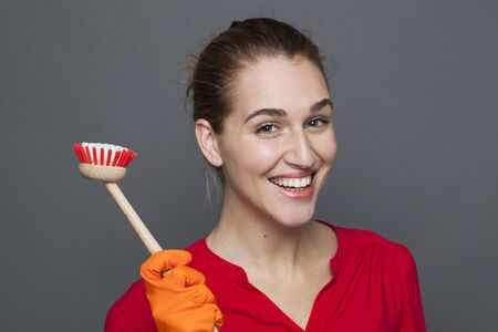 fun cleaning concept - attractive 20s girl holding a dish brush with pride for efficient and satisfying housekeeping,studio shot