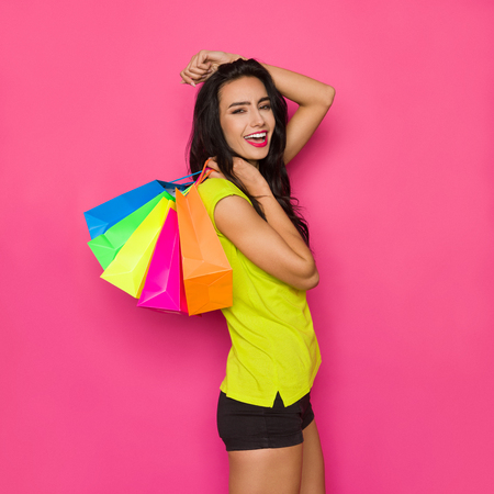 Photo for Happy beautiful young woman in vibrant green shirt and black shorts is holding colorful shopping bags on her shoulder and shoutng. Three quarter length studio shot on pink background. - Royalty Free Image