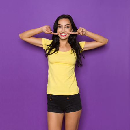 Photo pour Young woman in yellow shirt and black shorts is pointing at her smile. Three quarter length studio shot on purple background. - image libre de droit