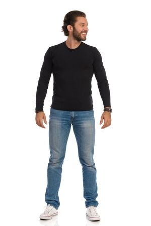 Photo pour Smiling handsome man in black jersey, jeans and sneakers is standing relaxed and looking at the side. Front view. Full length studio shot isolated on white. - image libre de droit