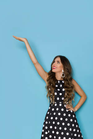 Photo pour Young woman in elegant black cocktail dress in polka dots pattern is holding hand raised, presenting something and looking up. Three quarter length studio shot against blue background. - image libre de droit