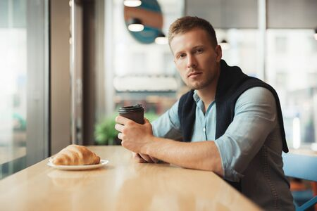 young handsome man having his croissant and drinking hot coffee for lunch in the cafe feeling calm