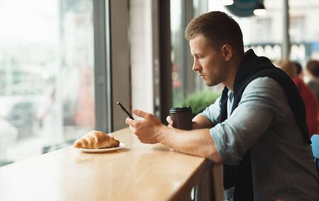 young handsome man having his croissant and drinking hot coffee for lunch in the cafe while texting message in smartphone