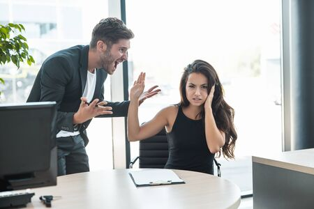 Photo pour strict boss man swearing at upset tired employee woman for bad work at the workplace looking angry - image libre de droit