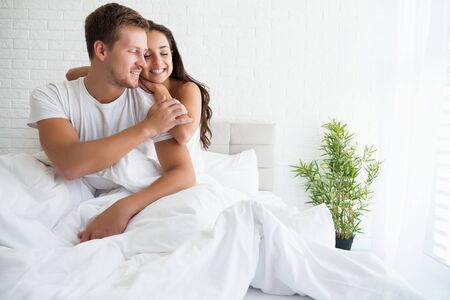 Photo pour young couple handsome man and beautiful brunette woman hugging each other in bed in bright bedroom feeling happy - image libre de droit