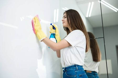 cute young woman in yellow gloves with detergent spray in her hand wiping dust off from the kitchen wall with a rag thoroughly