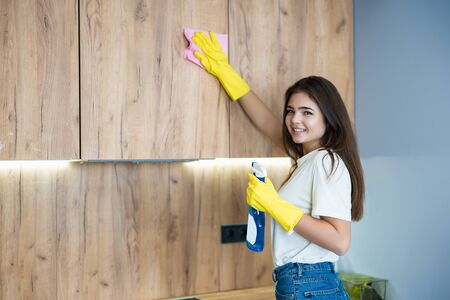 beautiful young woman in yellow gloves with detergent spray in her hand thoroughly wiping dust off from the kitchen cabinet with a rag