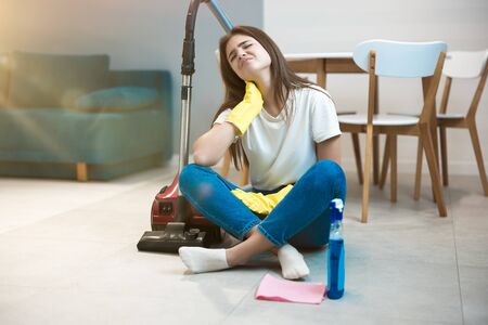 beautiful young woman in yellow gloves sitting with the vacuum cleaner in the middle of the livingroom suffering from neck pain