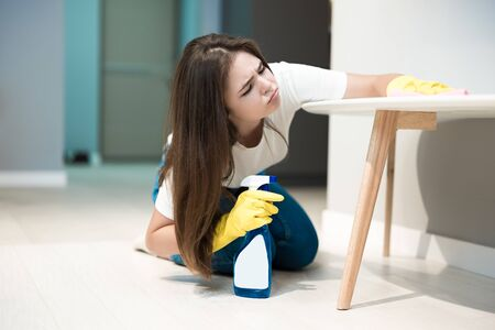 young brunette woman in yellow gloves with detergent spray in her hand wiping dust off from the kitchen chair with a rag looking tired
