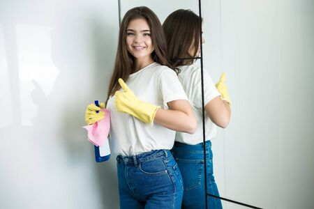 beautiful young smiling woman in yellow gloves with detergent spray and rag in her hand showing ok sign