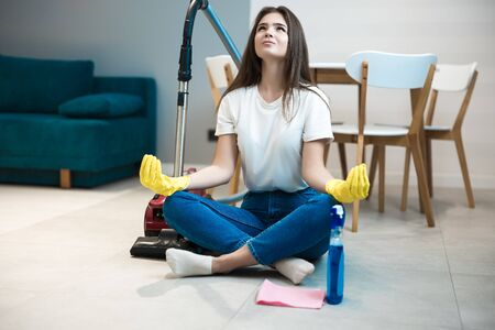 beautiful young brunette woman in yellow gloves sitting with the vacuum cleaner in the middle of the livingroom in peaceful yoga position