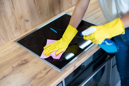 process of cleaning. woman's hands in yellow gloves using detergent spray wiping dust off from the kitchen hob with a rag.
