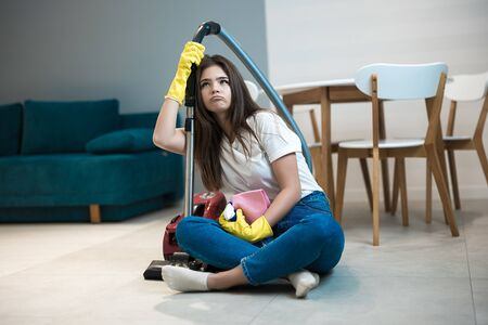 beautiful young woman in yellow gloves sitting with the vacuum cleaner in the middle of the livingroom looking tired