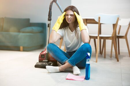 beautiful young woman in yellow gloves sitting with the vacuum cleaner in the middle of the livingroom looking exhausted
