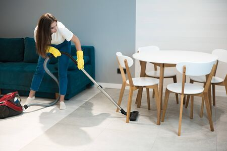 cute young woman in yellow gloves doing vacuum cleaning under the kitchen table
