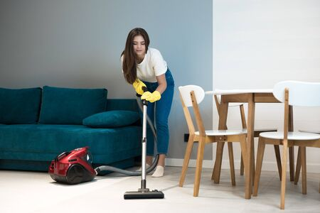 beautiful young woman in yellow gloves doing vacuum cleaning near the kitchen table