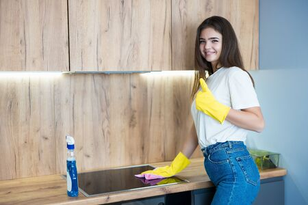 beautiful young woman in yellow gloves using detergent spray to wipe dust off from the kitchen hob with a rag