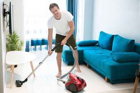 handsome smiling young man doing vacuum cleaning in the living room house chores