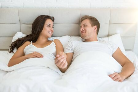 Photo pour happy young couple handsome man and beautiful woman lying in bed in bright bedroom smiling to each other feeling love family morning idyll - image libre de droit