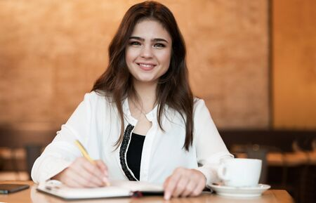 Photo pour young beautiful woman taking notes to her planner working outside office drinking hot coffee in the cafe multitasking modern businesswoman - image libre de droit