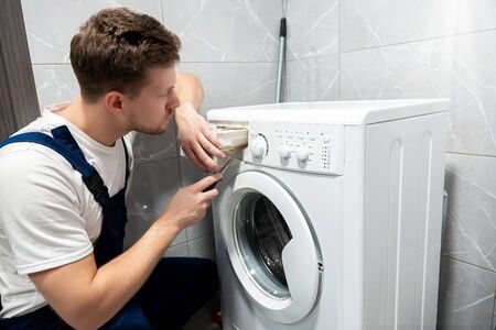 Photo pour young handsome man worker in uniform repairing washing machine at home in the toilette professional repair service - image libre de droit