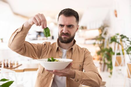 Photo for bearded man holding plate of salad in one hand and green leaf in another looking unset with his food during lunchn in cafe, vegan concept - Royalty Free Image