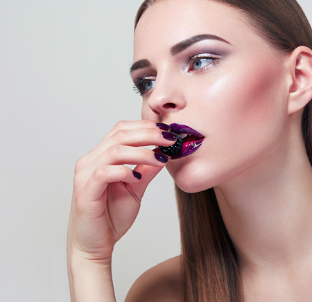 The girl in a beautiful face eating a berry. Beautiful expressive makeup on the face of the girl. The girl\'s face close up. Lilac lipstick. The girl in the studio on a white background.