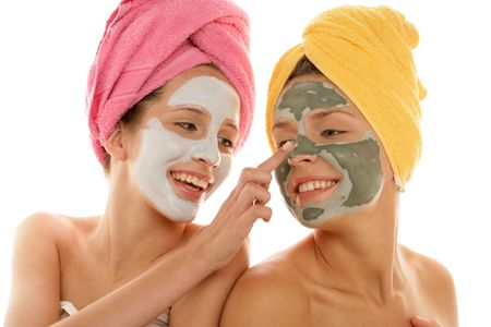 Two teenage girls applying facial cream isolated on white backgroundの写真素材