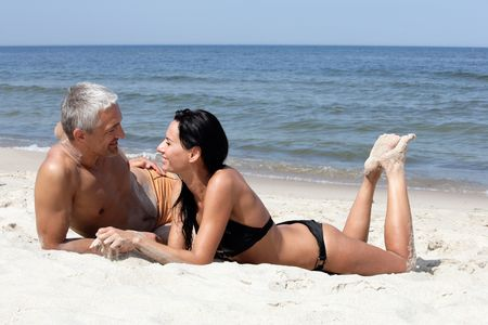 Attractive mature couple relaxing on the beachの写真素材