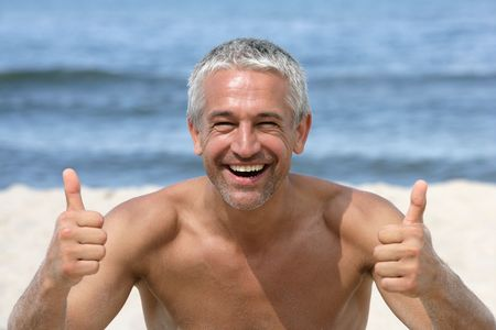 Photo pour Handsome happy man giving thumbs up on the beach - image libre de droit