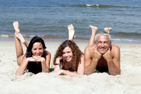 Family lying on sandy beach