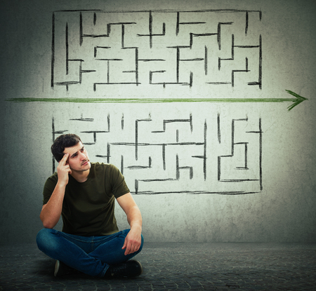Photo pour Man sitting on the floor hard thinking, find a solution to solve problem and escape from labyrinth. Breaking the rules, as a green arrow pierce the maze walls. Different imagination, alternative idea. - image libre de droit